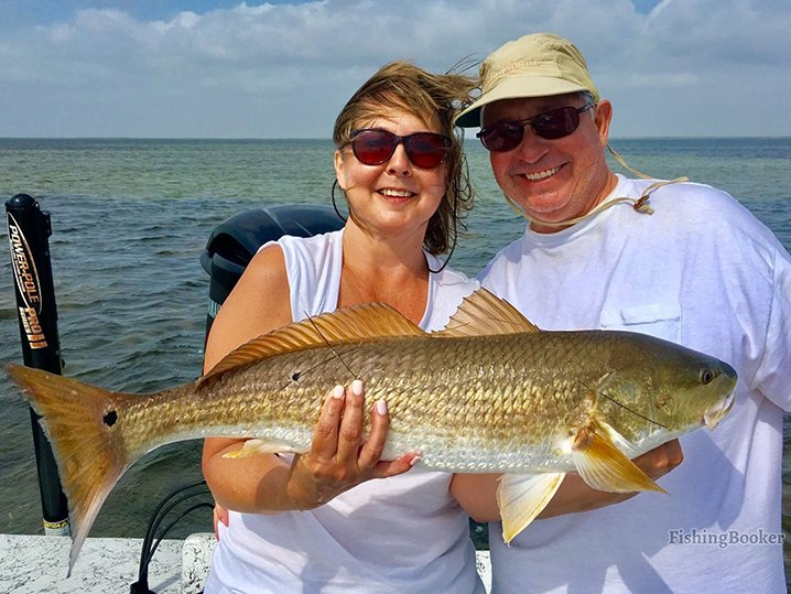 A couple on their summer fishing trip out of South Padre Island holding a big Redfish.