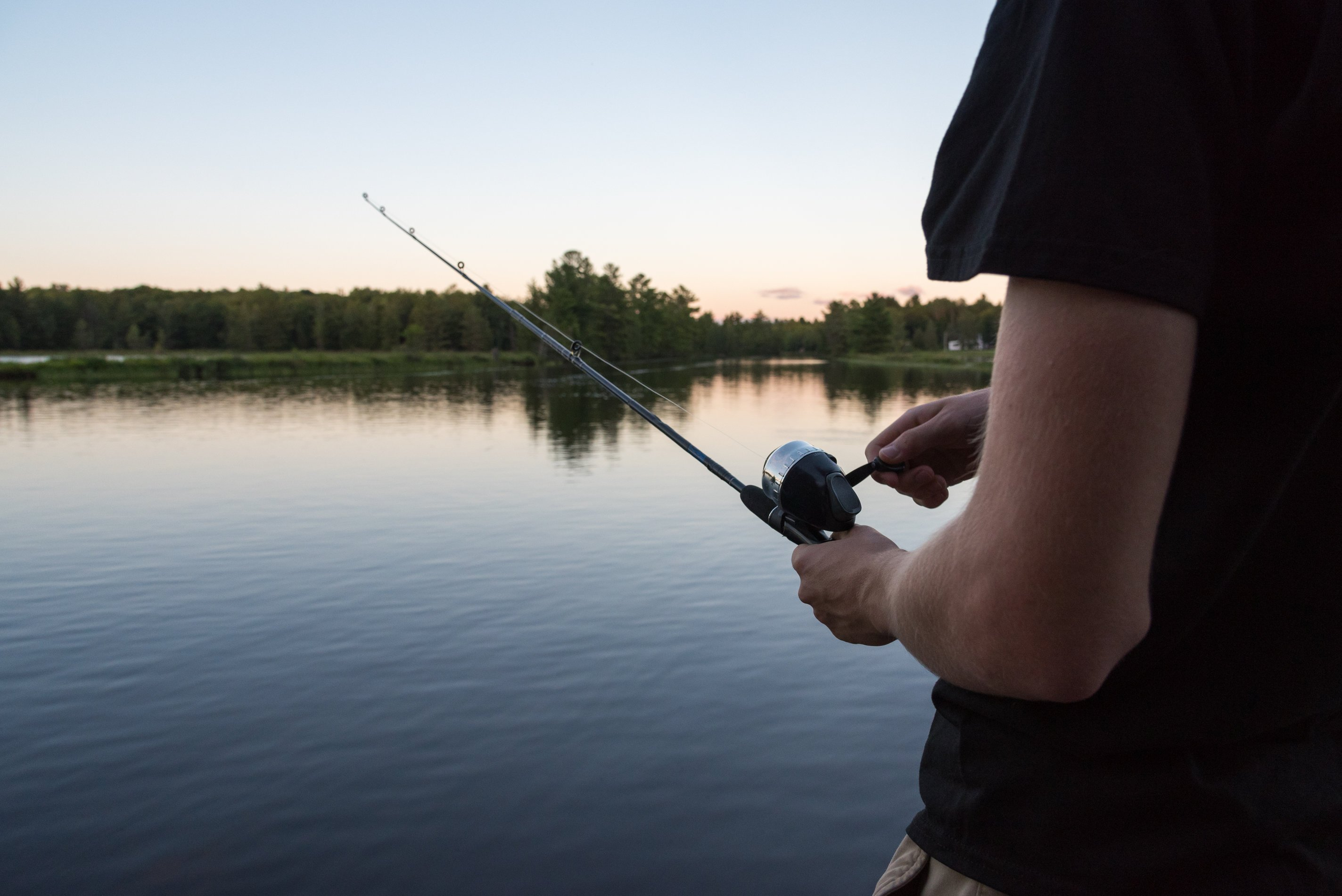 an angler holding a rod with his hand on the spincast fishing reel, and a river in the background
