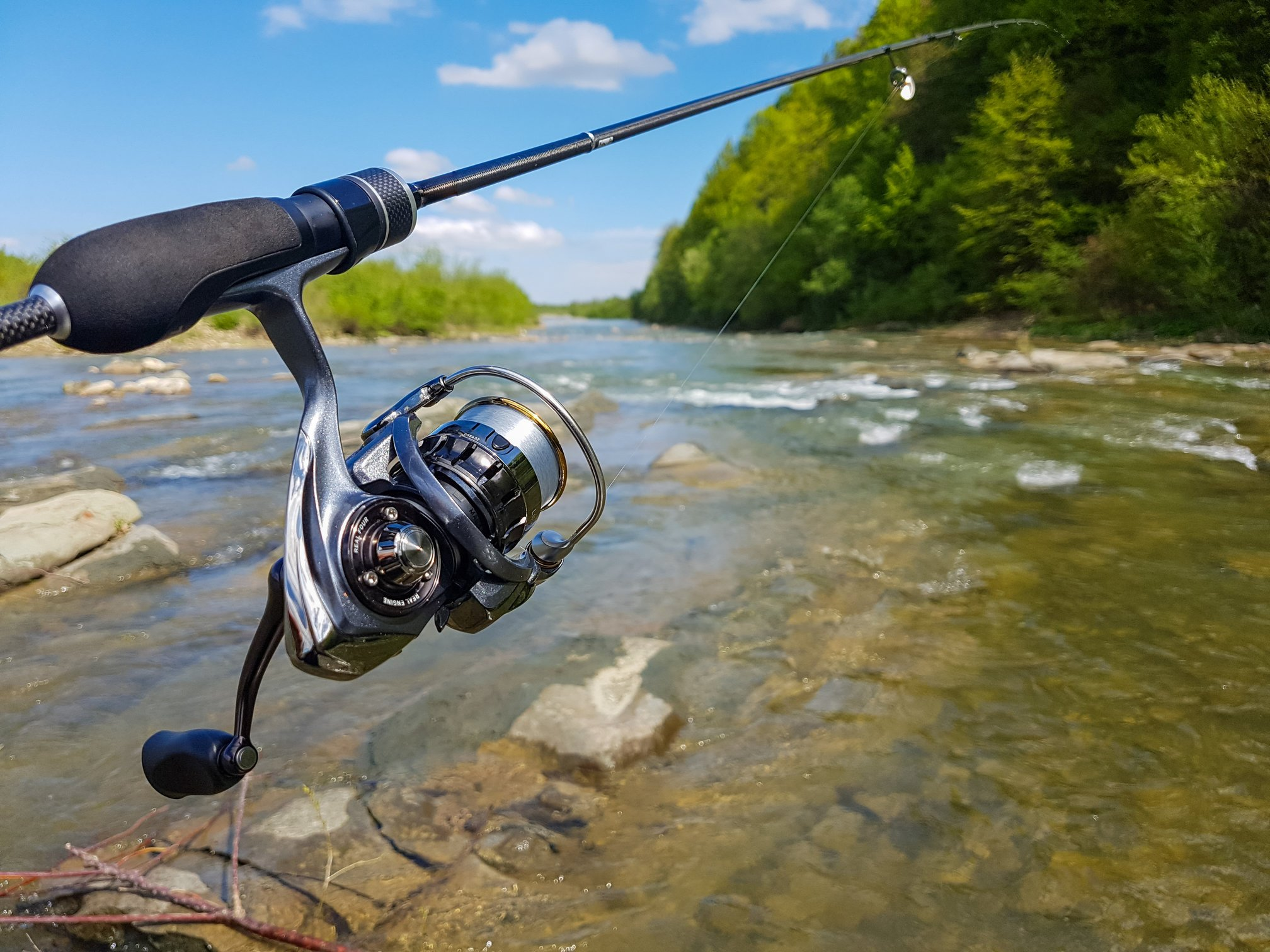 a closeup of a spinning reel on a fishing rod with a river in the background