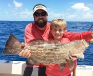 A young boy and a charter captain holding a big Gag Grouper they caught fishing in the Gulf of Mexico.