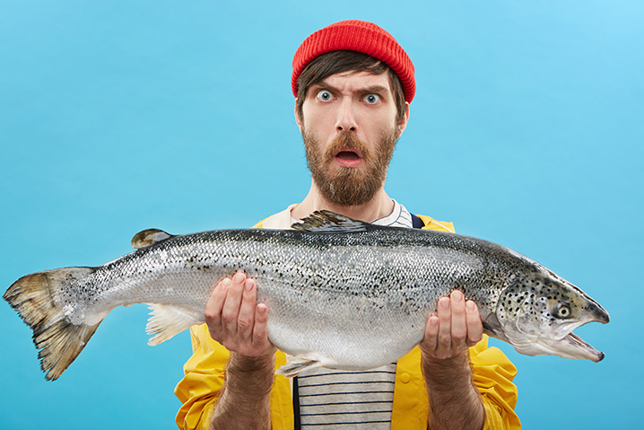 The photo showing a person with a red cap wearing a yellow jacket and holding trout with a funny expression on his face