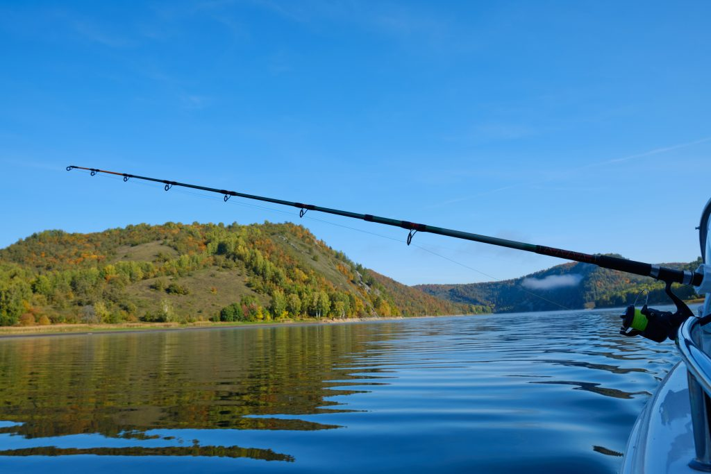 trolling on a lake: a fishing rod out on a moving boat