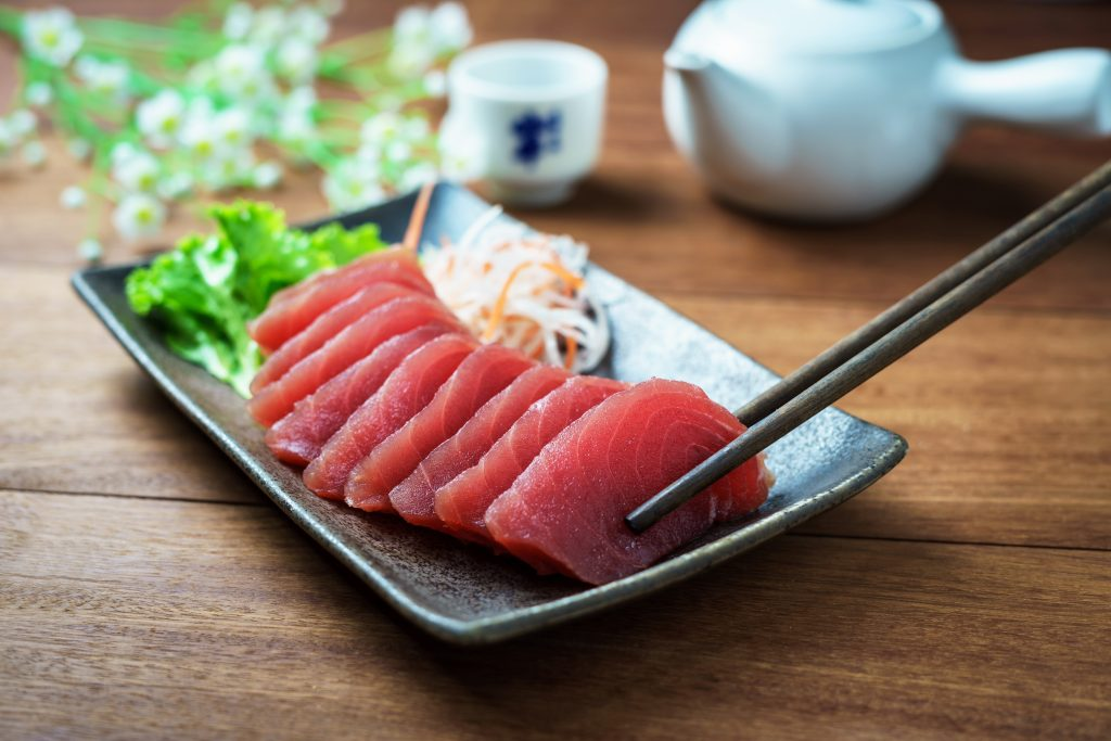Fresh tuna sahimi, one of the most popular types of tuna, laid on a plate with chopsticks holding one piece
