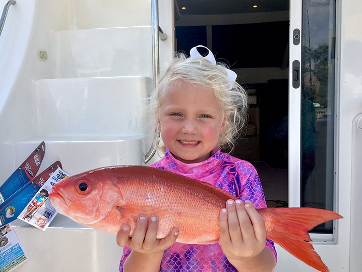 A little smiling girl holding Vermillion Snapper aboard a Destin fishing party boat